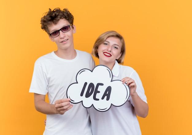 Jovem casal, homem e mulher, juntos, sorrindo, felizes e positivos, segurando um cartaz de bolha do discurso com a ideia da palavra sobre a parede laranja