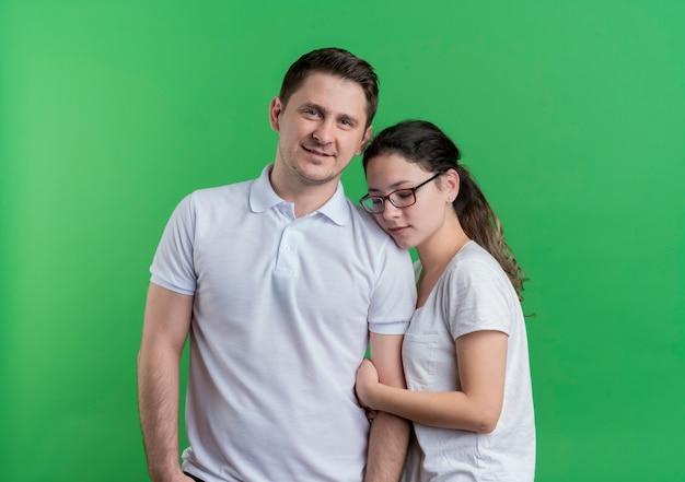 Jovem casal, homem e mulher, juntos, sorrindo, felizes e positivos sobre a parede de luz