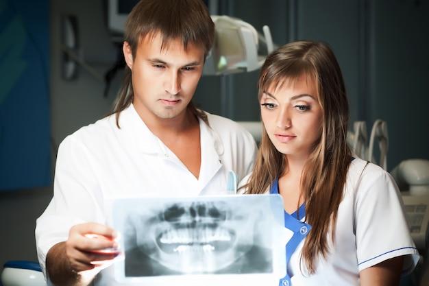 Jovem casal homem e mulher na clínica odontológica, olhando para a foto dental