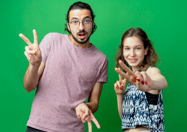 Jovem casal, homem e mulher, olhando para a câmera sorrindo, mostrando o sinal da vitória em pé sobre um fundo verde