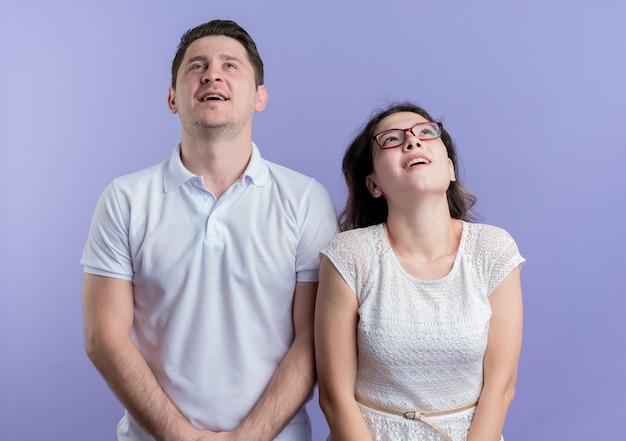 Jovem casal, homem e mulher, olhando para cima, sorrindo e pensando em pé sobre uma parede azul
