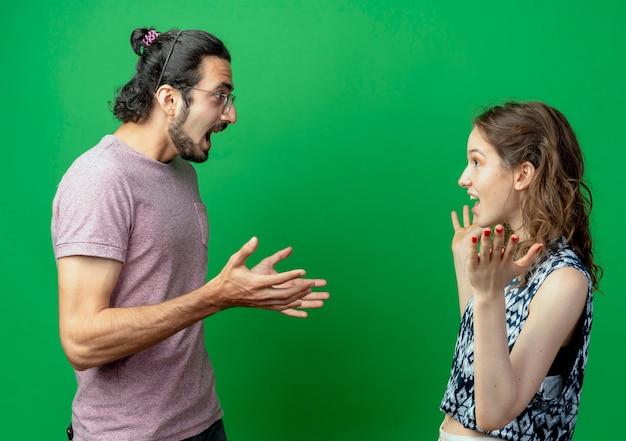 Jovem casal, homem e mulher, olhando um para o outro, felizes e animados, em pé sobre um fundo verde