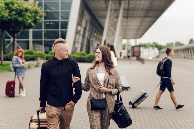 Jovem casal, homem e mulher perto do aeroporto com uma mala