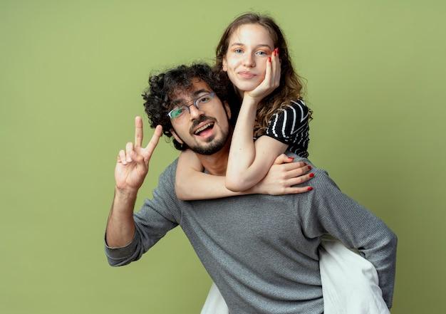 Jovem casal homem e mulher se divertindo juntos, homem carregando a namorada nas costas sobre a parede verde