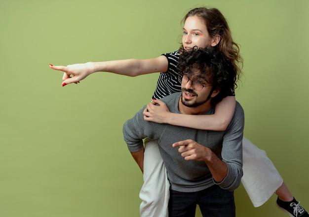 Jovem casal homem e mulher se divertindo juntos, homem carregando sua namorada nas costas enquanto uma mulher aponta com o dedo para algo sobre a parede verde