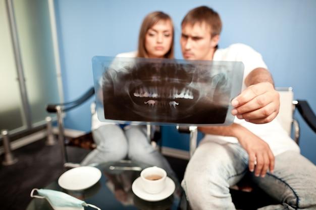 Jovem casal homem e mulher sentada na clínica odontológica, olhando a foto dental e bebendo chá