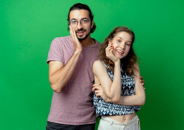 Jovem casal homem e mulher sorrindo, felizes e positivos, em pé sobre a parede verde