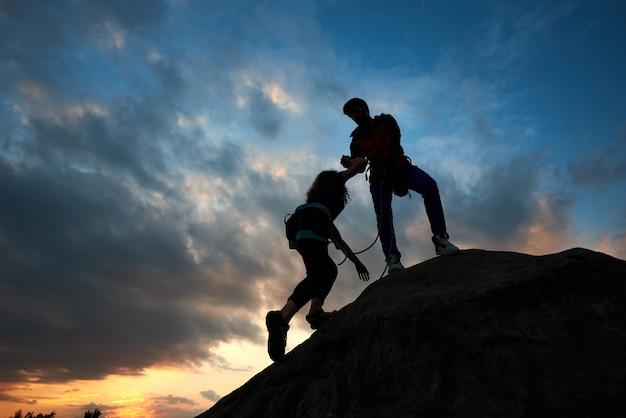 Jovem casal homem e mulher subindo na pedra. mão amiga. silhuetas no fundo por do sol.