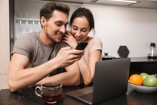 Jovem casal homem e mulher usando laptop com smartphone, enquanto está sentado na cozinha