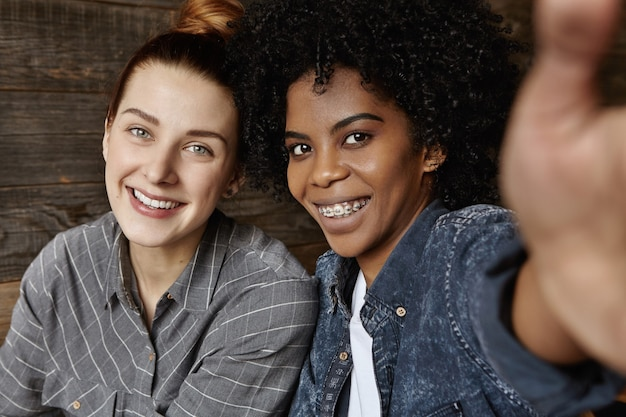 Jovem casal homossexual inter-racial feliz posando na parede de madeira para uma selfie