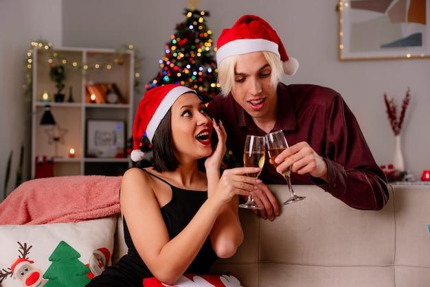 Jovem casal impressionado em casa na época do natal com chapéu de papai noel segurando uma taça de champanhe