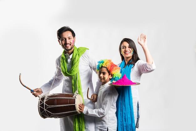 Jovem casal indiano com criança comemorando o festival de holi. dançando, tocando bateria e segurando um prato cheio de cores
