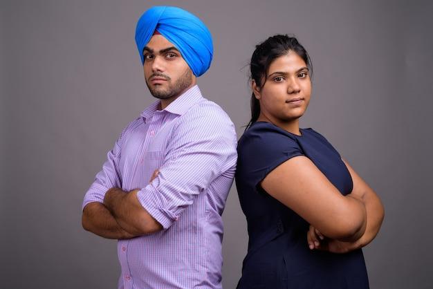 Jovem casal indiano junto e apaixonado contra uma parede cinza
