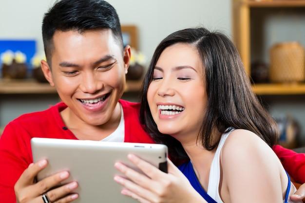Jovem casal indonésio - homem e mulher - sentado com um computador tablet no sofá