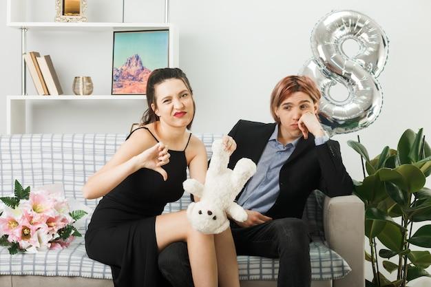 Jovem casal insatisfeito com o polegar no dia da mulher feliz com o ursinho de pelúcia sentado no sofá da sala