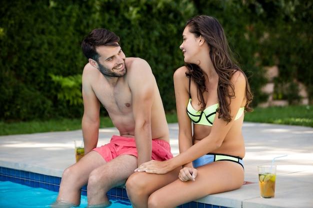 Jovem casal interagindo à beira da piscina em um dia ensolarado
