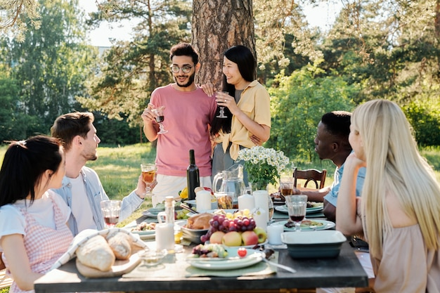 Jovem casal intercultural feliz com taças de vinho tinto anunciando seu noivado para amigos reunidos à mesa para jantar ao ar livre