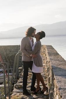 Jovem casal interracial adulto em uma praia, homem caucasiano e mulher afro-americana em roupas casuais, aproveitando o dia de verão na costa do mar