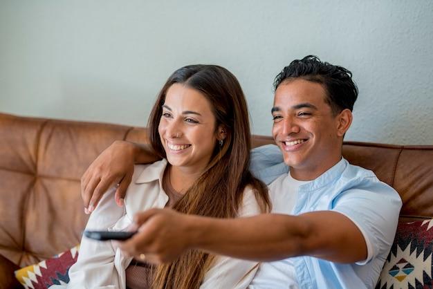 Jovem casal interracial assistindo tv juntos, sentados no sofá em casa - vida de casal e estilo de vida feliz pessoas tendo com filme - atividade de lazer interna menino negro e menina caucasiana apaixonada Foto Premium
