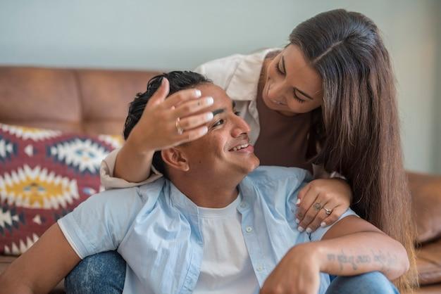 Jovem casal interracial caucasiano negro apaixonado em casa, sentado no sofá, sorrindo e se olhando juntos em um relacionamento - homem e mulher milenar do estilo de vida interior feliz e bonito