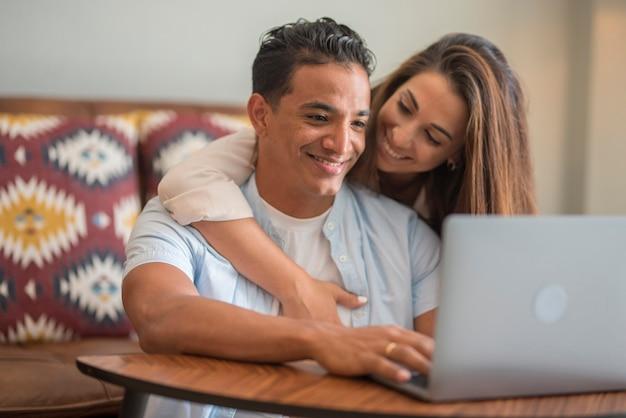 Jovem casal interracial relaxando no sofá com o laptop. pessoas apaixonadas e felizes, estilo de vida de lazer em casa juntos - homem e mulher desfrutam do computador e do trabalho moderno online