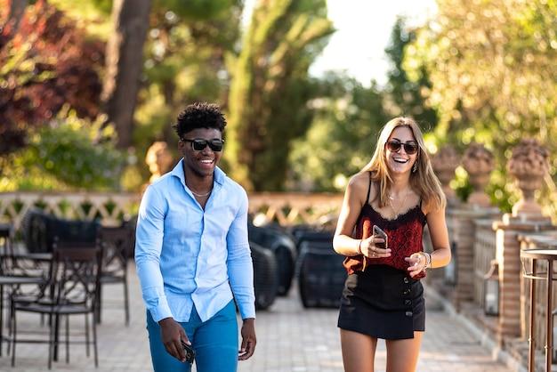 Jovem casal interracial se divertindo enquanto caminhava. menina negra do sexo masculino e branco.