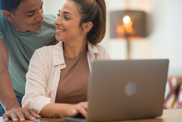 Jovem casal interracial trabalhando junto com o laptop. pessoas estilo de vida em casa juntos usando conexão de internet - homem e mulher desfrutam de computador e trabalho moderno online grátis e feliz
