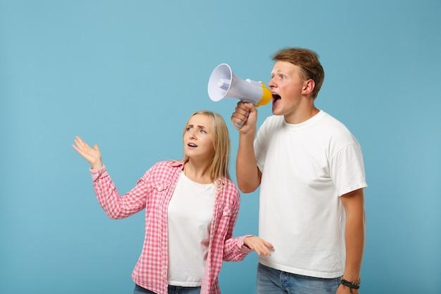Jovem casal intrigado, dois amigos, cara e mulher, em camisetas brancas rosa vazias posando