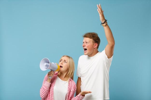 Jovem casal irritado, dois amigos, cara e mulher, em camisetas brancas rosa posando