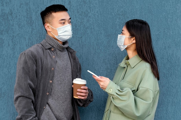 Jovem casal japonês usando máscara