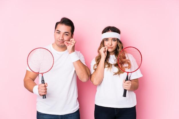 Jovem casal jogando badminton isolado com os dedos nos lábios, mantendo um segredo.