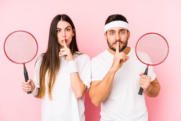 Jovem casal jogando badminton isolado mantendo um segredo ou pedindo silêncio.