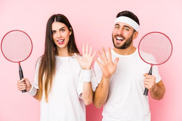 Jovem casal jogando badminton isolado sorrindo alegre mostrando o número cinco com os dedos.