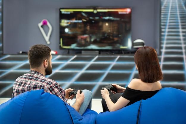 Jovem casal jogando no computador com um playstation, sentado em cadeiras em um clube de jogos com os controles nas mãos, uma visão traseira da tela da tv