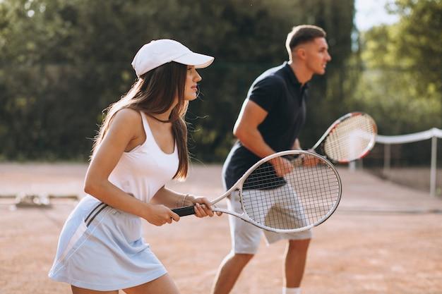 Jovem casal jogando tênis na quadra