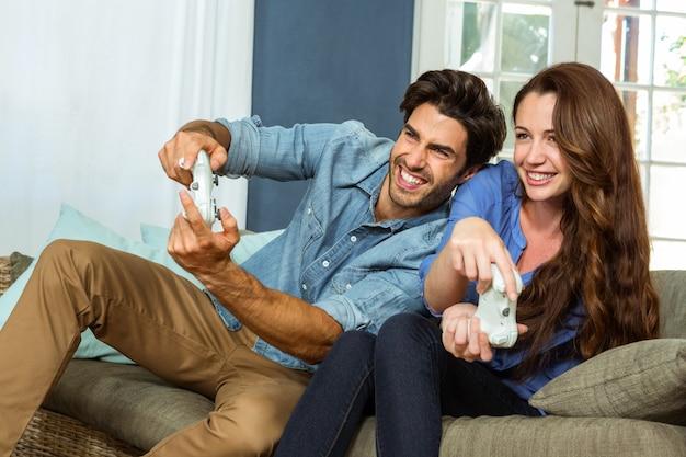 Jovem casal jogando videogame enquanto está sentado no sofá