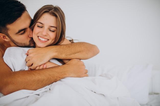 Jovem casal junto deitado na cama