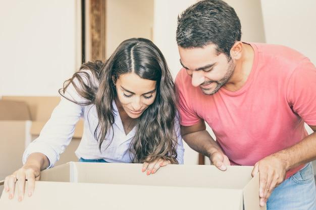 Jovem casal latino animado e feliz abrindo a caixa de papelão e olhando dentro, movendo e desempacotando coisas