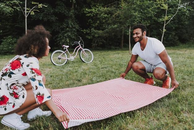 Jovem casal latino colocar toalha de mesa para piquenique