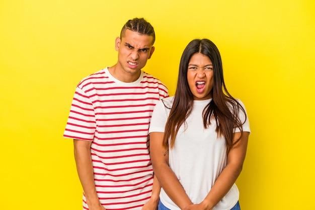 Jovem casal latino isolado em um fundo amarelo, gritando muito zangado e agressivo.