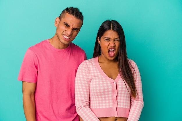 Jovem casal latino isolado na parede azul, gritando muito zangado e agressivo.