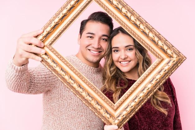 Jovem casal latino segurando um quadro