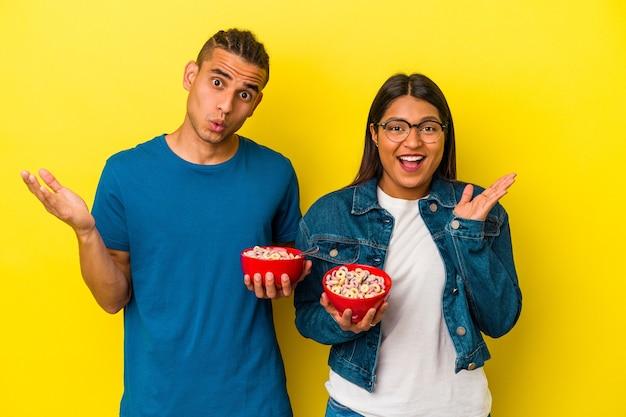 Jovem casal latino segurando uma tigela de cereais isolada em fundo amarelo surpreso e chocado.