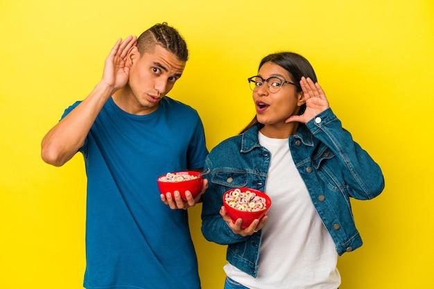 Jovem casal latino segurando uma tigela de cereais isolada em fundo amarelo, tentando ouvir uma fofoca.