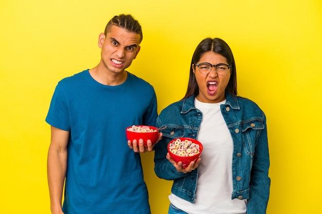 Jovem casal latino segurando uma tigela de cereais isolada na parede amarela, gritando muito zangado e agressivo.