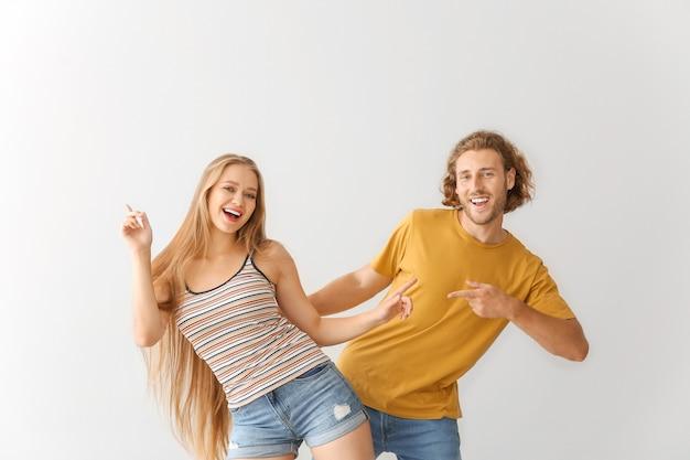 Jovem casal legal dançando contra o branco