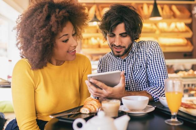 Jovem casal legal em uma padaria, tomando um café da manhã e usando um tablet.