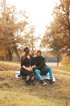 Jovem casal legal homem tocando a barriga da esposa no parque