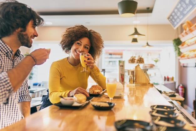 Jovem casal legal tomando um café da manhã, eles estão bebendo chá e café em uma padaria