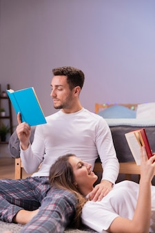 Jovem casal lendo juntos na cama